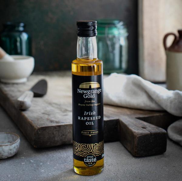 Newgrange Gold Irish Rapeseed Oil in front of kitchen chopping board