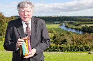 John Rogers holding bottles of Newgrange Gold rapeseed oil above river Boyne