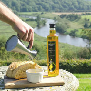 pouring newgrange gold oil in dish overlooking Boyne valley