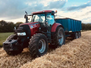 red tractor pulling truck after harvesting at Newgrange Gold