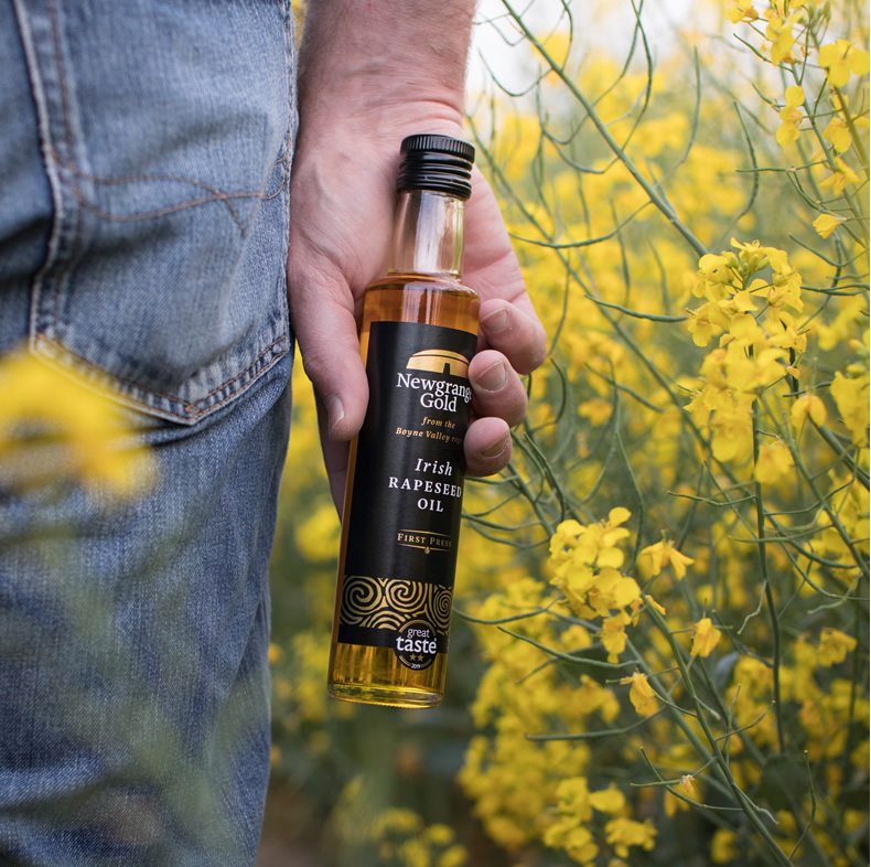 Bottle Newgrange Gold Irish Rapeseed Oil being held by man in rapeseed field