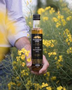 Jack Rogers holding bottle Newgrange Gole Irish Rapeseed Oil among rapeseed